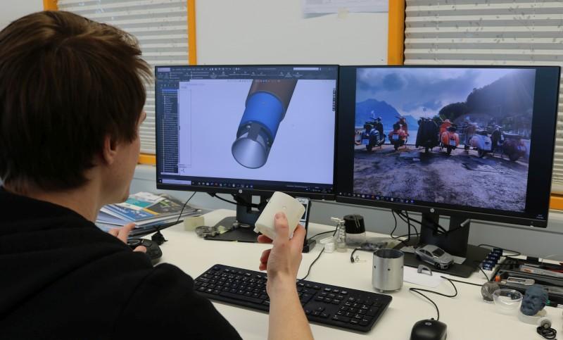 Konstrukteur Martin Odermatt am CAD und mit dem gedruckten Teil.